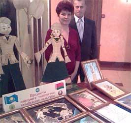 Л.Сазонова и В.Жданович около выставки предметов народного творчества белорусской культуры.
